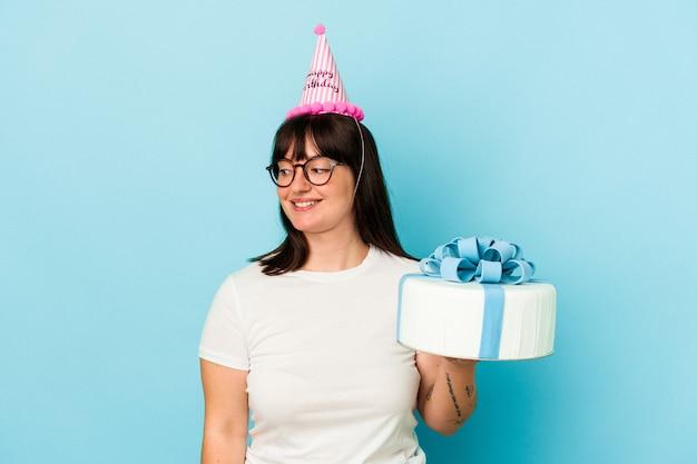Jeune femme bien roulée célébrant son anniversaire isolée sur fond bleu regarde de côté souriante, gaie et agréable.