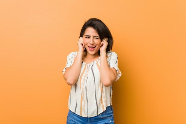 Jeune femme bien roulée couvrant les oreilles avec les mains.