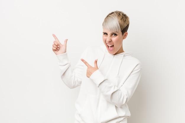 Jeune femme bien roulée portant un sweat à capuche blanc pointant avec les index vers un espace de copie, exprimant l'excitation et le désir.