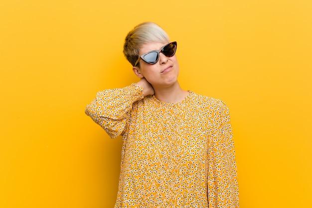 Jeune femme bien roulée portant des vêtements d'été floraux souffrant de douleurs au cou dues à un style de vie sédentaire.