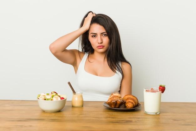 Jeune femme bien roulée prenant un petit déjeuner choquée, elle se souvient d'une réunion importante.