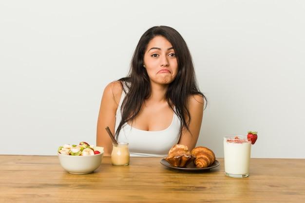 Jeune femme bien roulée prenant un petit déjeuner hausse les épaules et les yeux ouverts confus