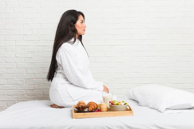 Jeune femme bien roulée prenant un petit déjeuner sur le lit en regardant à gauche, pose de côté.