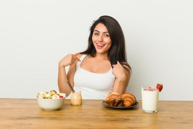 Jeune femme bien roulée prenant un petit déjeuner surpris en pointant avec le doigt, souriant largement.