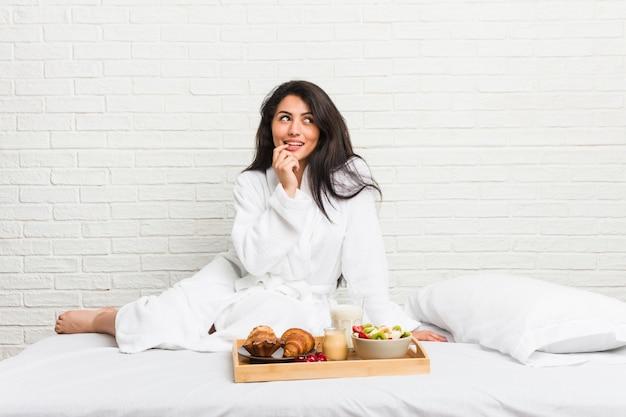 Jeune femme bien roulée prenant son petit déjeuner sur le lit détendue pensant à quelque chose