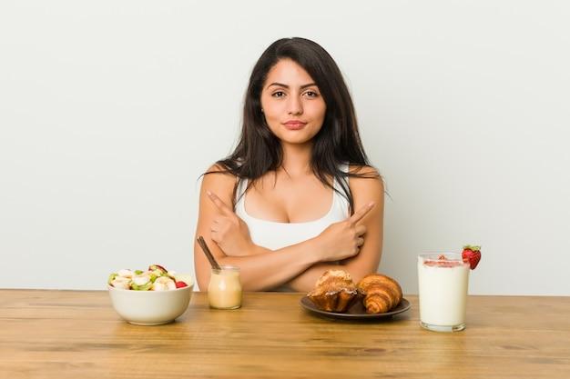 Une jeune femme bien roulée prenant son petit déjeuner en pointe, essaie de choisir entre deux options.