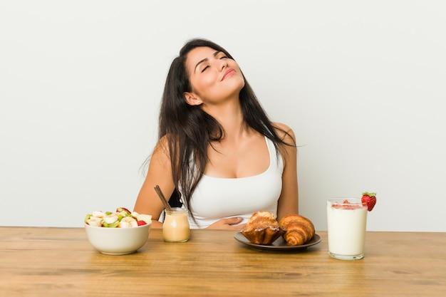 Jeune femme bien roulée prenant son petit-déjeuner touche le ventre, sourit doucement, concept de restauration et de satisfaction.