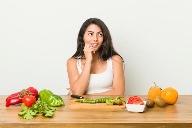 Jeune femme bien roulée préparant un repas sain détendue pensant à quelque chose en regardant un.