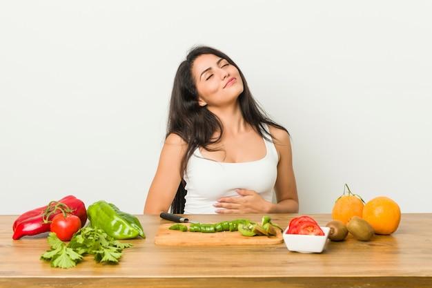 Jeune femme bien roulée préparant un repas sain touche le ventre, sourit doucement, concept de restauration et de satisfaction.