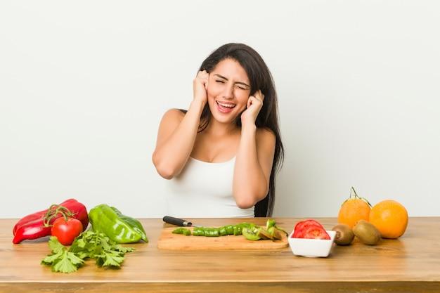 Jeune femme bien roulée prépare un repas sain couvrant les oreilles avec les mains