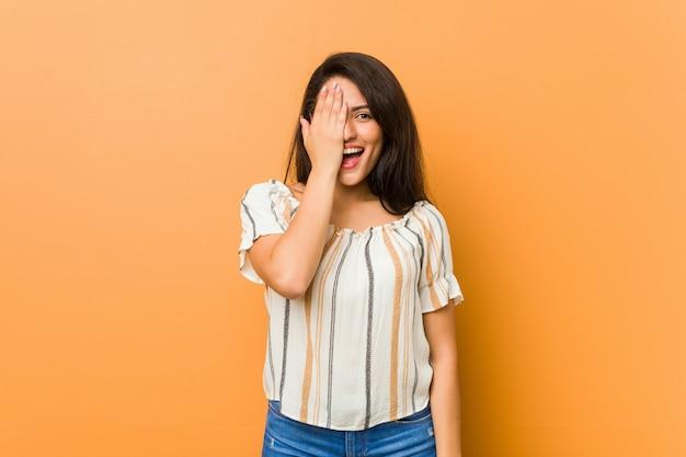 Jeune femme bien roulée s'amuser couvrant la moitié du visage avec la paume.