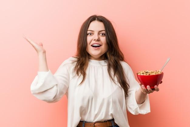 Jeune femme bien roulée taille plus tenant un bol de céréales célébrant une victoire ou un succès