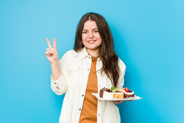 Jeune femme bien roulée tenant un gâteaux sucrés montrant le numéro deux avec les doigts.