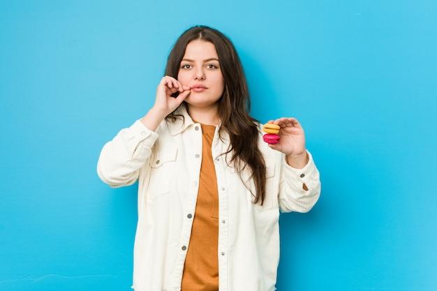 Jeune femme bien roulée tenant des macarons avec les doigts sur les lèvres en gardant un secret.