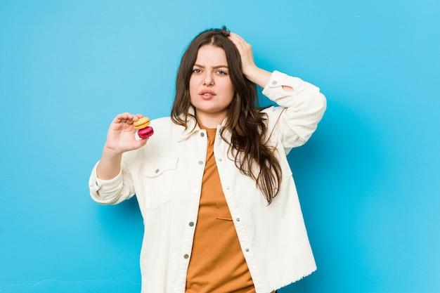 Jeune femme bien roulée tenant des macarons étant choquée, elle s'est souvenue d'une réunion importante.