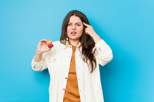 Jeune femme bien roulée tenant des macarons montrant un geste de déception avec l'index.