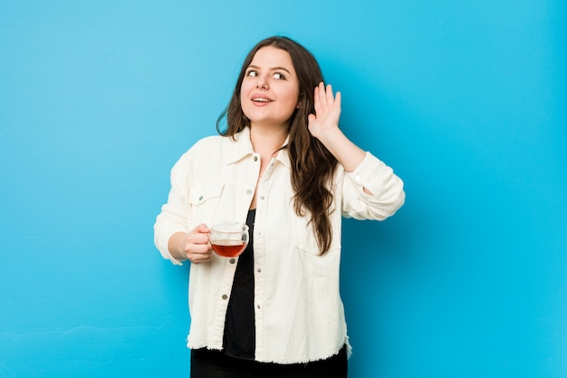 Jeune femme bien roulée tenant une tasse de thé en essayant d'écouter les potins.
