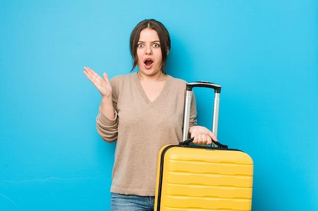 Jeune femme bien roulée tenant une valise surpris et choqué