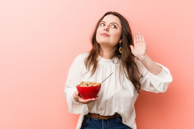 Jeune femme bien taille, curvy, tenant un bol de céréales en essayant d'écouter un commérage.
