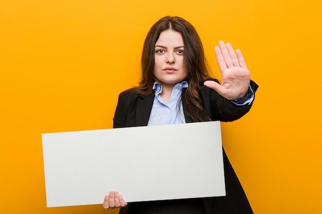 Jeune femme bien taille, curvy, tenant une pancarte debout, la main tendue, montrant un panneau d'arrêt vous empêchant.