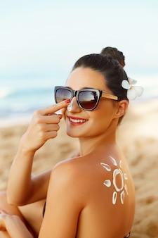 Jeune femme en bikini appliquant une crème solaire solaire.