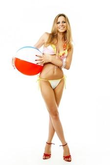 Jeune femme en bikini avec un ballon de plage isolé sur fond blanc