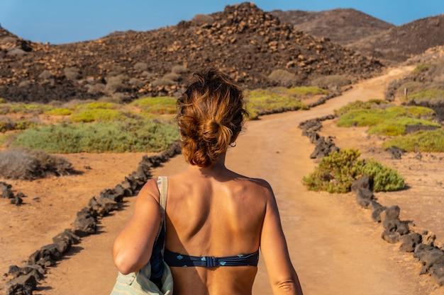 Une jeune femme avec un bikini bleu sur le sentier au nord de l'isla de lobos, à côté de la côte nord de l'île de fuerteventura, aux canaries. espagne