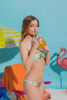Jeune femme en bikini avec boisson