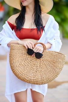 Jeune femme en bikini et chemise blanche tenant un sac en osier et des lunettes de soleil quoi debout sur la plage