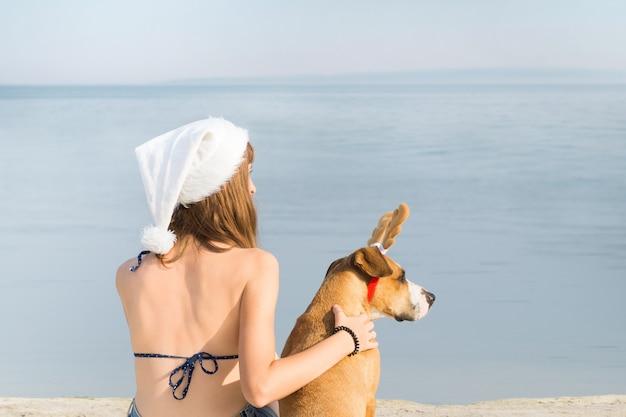 Jeune femme en bikini et chien au bord de mer pour les vacances de noël