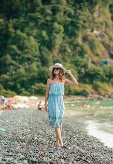 Jeune femme en bikini de couleur appréciant la danse de l'été. femme en train de bronzer au bord de la mer. vacances d'été, vacances, détendez-vous. fille de soleil sur la plage en maillot de bain