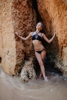 Jeune femme en bikini noir posant sur un sable rocheux près de la mer