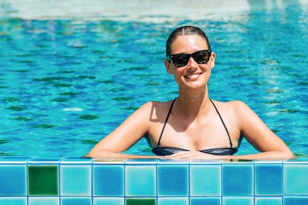 Jeune femme en bikini noir se détendre dans la piscine de l'hôtel