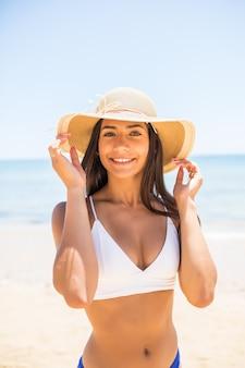Jeune femme en bikini portant un chapeau de paille blanc, profitant des vacances d'été à la plage. portrait de la belle femme latine se détendre à la plage avec des lunettes de soleil.