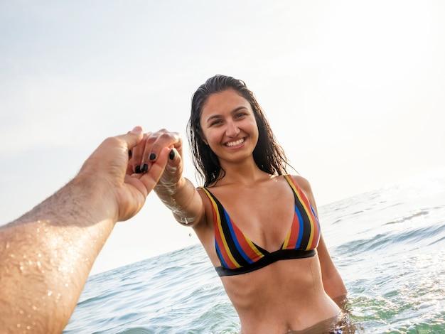 Jeune femme en bikini prend un bain dans la mer aux lumières du coucher du soleil en été. suivez-moi la pose.
