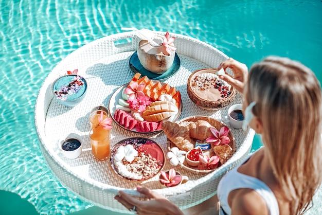 Jeune femme en bikini avec table flottante remplie de différents aliments tropicaux passe un bon moment à nager dans une piscine.