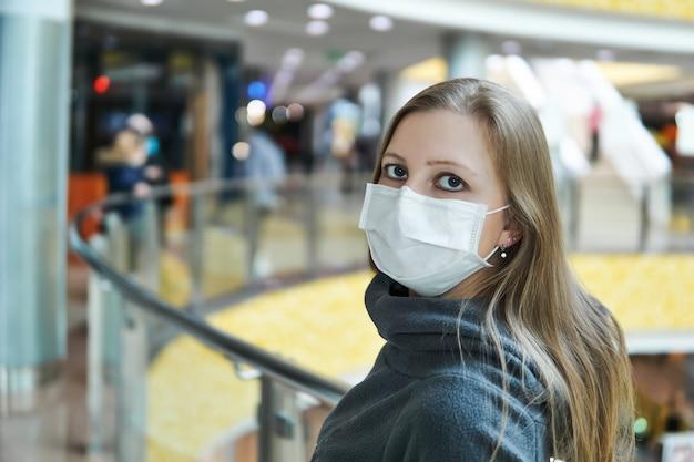Jeune femme blanche en masque chirurgical dans un espace public