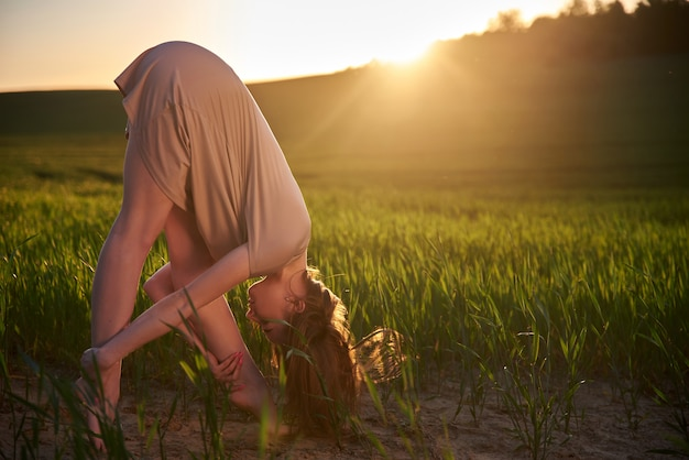 Jeune femme blanche pratiquant le yoga, dans la nature dans un champ d'herbe verte en été au coucher du soleil. étirements, méditation, énergie solaire. art-thérapie, relaxation.