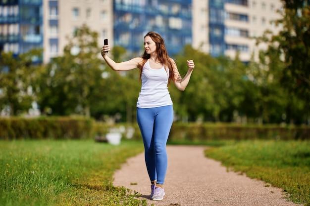 Une jeune femme blanche prend des photos d'elle-même en train de faire du jogging à l'aide d'un smartphone