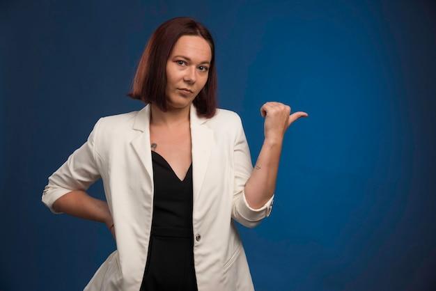 Jeune femme en blazer blanc faisant bon signe.