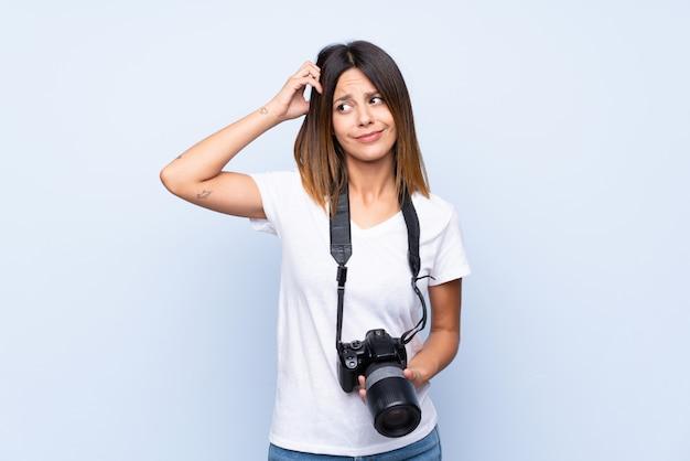 Jeune femme sur bleu isolé avec une caméra professionnelle et pensant