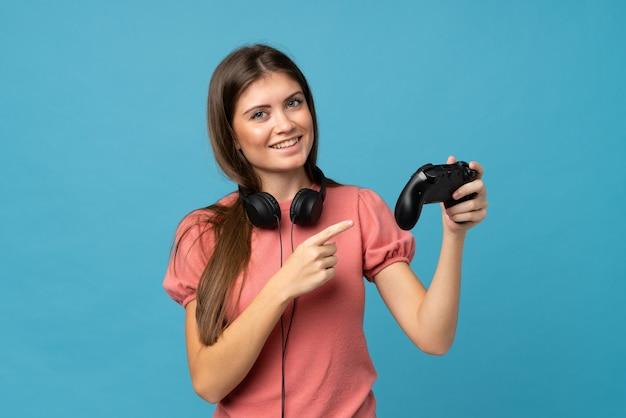 Jeune femme sur bleu isolé jouant à des jeux vidéo