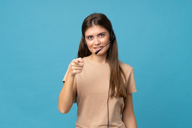 Jeune femme sur bleu isolé pointant vers l'avant