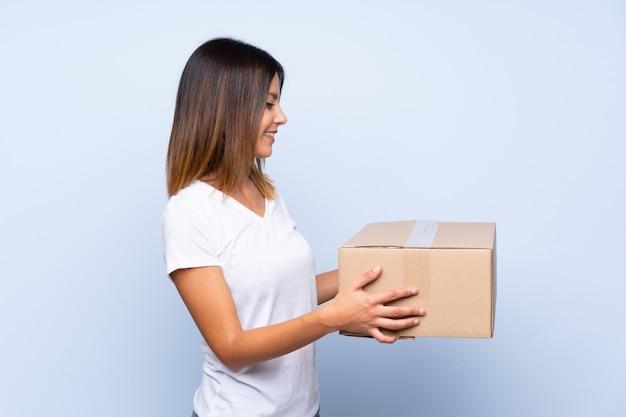 Jeune femme sur bleu isolé tenant une boîte pour la déplacer sur un autre site