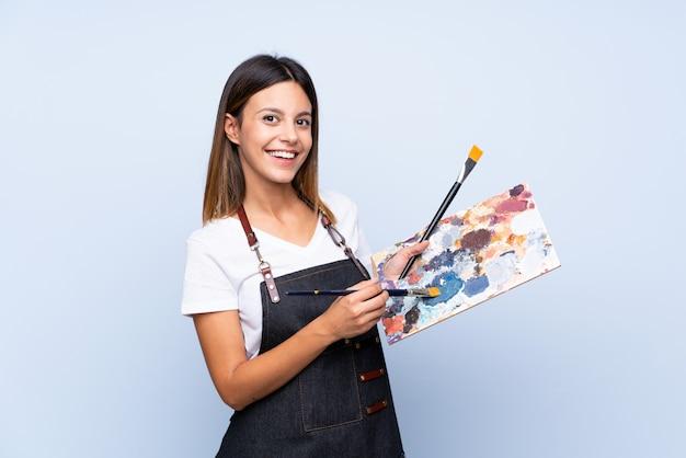 Jeune femme sur bleu isolé tenant une palette