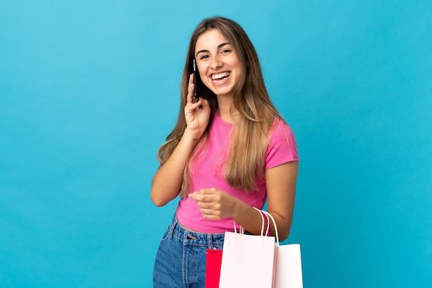 Jeune femme sur bleu isolé tenant des sacs à provisions et appeler un ami avec son téléphone portable
