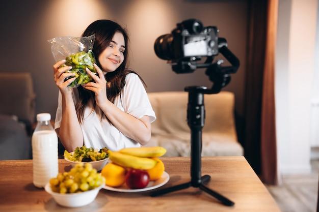 Jeune femme blogueuse alimentation saine cuisine fraîche de fruits salade végétalienne en studio de cuisine, tutoriel de tournage à la caméra pour chaîne vidéo. une jeune influenceuse montre son amour pour une alimentation saine.