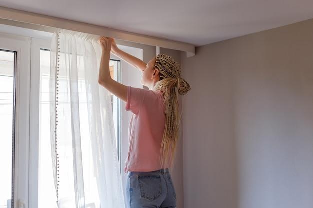 Jeune femme blonde accrocher des rideaux à la fenêtre
