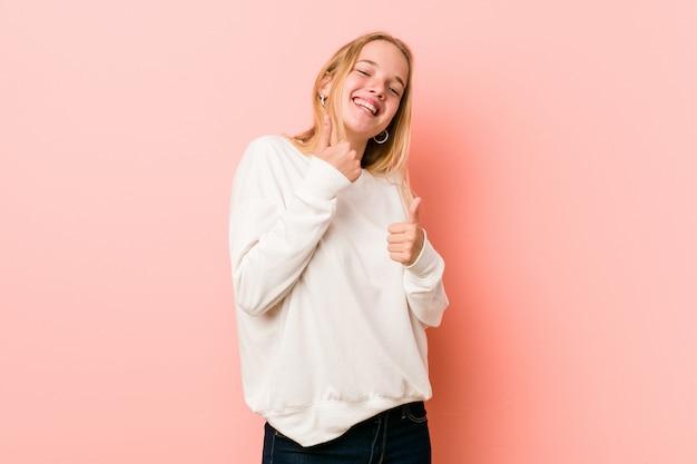 Jeune femme blonde adolescente levant les deux pouces vers le haut, souriant et confiant.