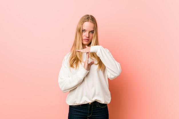 Jeune femme blonde adolescente montrant un geste de temporisation.